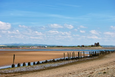 A view of Piel island & Castle from Walney Island, Cumbria, England. Remains of old pier in the foreground