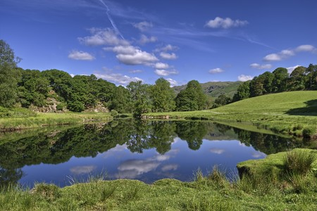 the lake district: Trees reflected in the river Brathay at Elterwater, the English Lake District Stock Photo