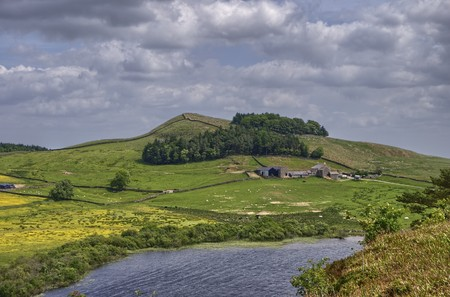 the crag: A view from Hadrians wall looking across Crag Lough to a farm on a hill