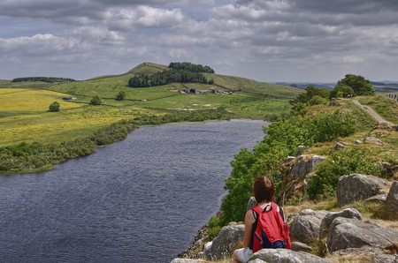the crag: A female hiker on Hadrians wall looking at the view across Crag Lough