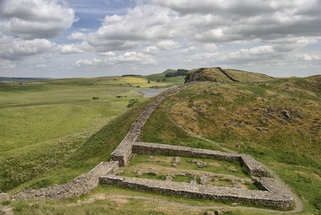 A view along Hadrians wall near Steel Rigg with Milecastle 39 in the foreground. Northumberland National Park Stock Photo