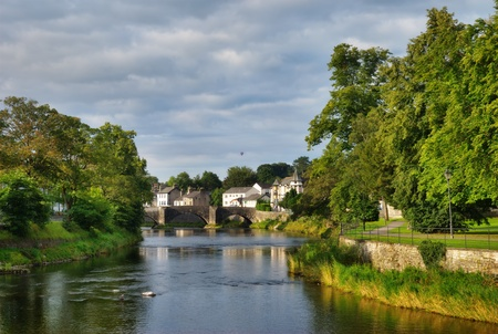 The River Kent, Kendal, Cumbria, England, with Nether bridge in the distance