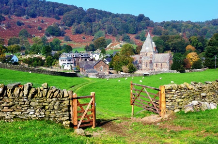 comida inglesa: Una vista rural de Inglaterra de pueblo y de la iglesia, Cumbria, Finsthwaite, con una puerta de la granja abierta en primer plano