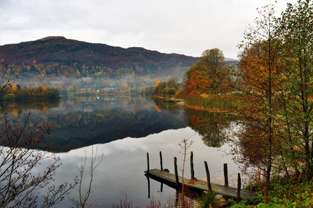 Still water on Grasmere with reflections of Autumn colours and a small landing jetty in the foreground