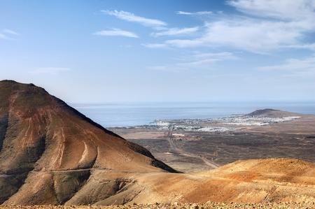 Scenic landscape of Lanzarote viewed from Los Ajaches mountains over Femes village to resort of Playa Blanca on coastline, Canary Islands, Spain.