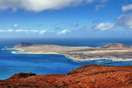 The Island of La Graciosa and the port of Caleta del Sebo taken from the Mirador del Rio, a famous viewpoint on Lanzarote, in the Spanish Canary Islands.
