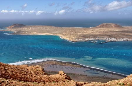 The Island of La Graciosa and the port of Caleta del Sebo taken from the Mirador del Rio, a famous viewpoint on Lanzarote, in the Spanish Canary Islands. Stock Photo - 9159247