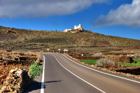 Highway receding on island of Lanzarote with white building on hill in background, Canary Islands, Spain. Stock Photo