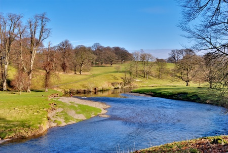 receding: Scenic view of river Kent flowing through Levens Park in Cumbria, England.background blue countryside cumbria distance england english fields flowing grass green kent landscape levens meandering nature outdoors outside park peaceful recedes receding river Stock Photo
