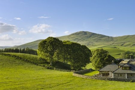 countryside background: A large house set in green, rural countryside with hills in the background.