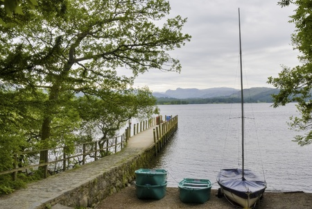 langdale pikes: A small wooden jetty and dinghy on the shore of Windermere at Brockhole  in the English Lake District National Park