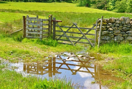 A wooden field gate reflected in puddle  in the English Lake District National Park photo