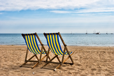 south west england: Two deckchairs on a sandy beach at Swanage, South West England