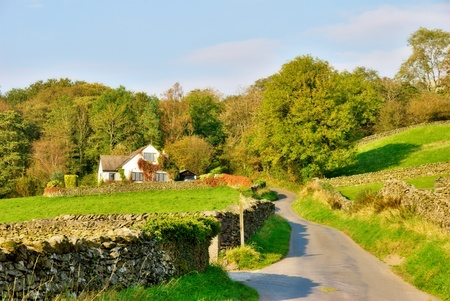 An English country lanelined with dry-stone walls, leading to a house