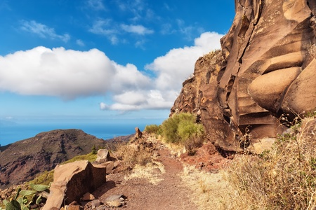 A mountain path bordered by red cliffs, Tenerife in the Spanish Canary Islands