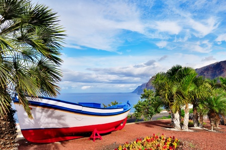tenerife: A colourful painted fishing boat on display near the ocean in Los Gigantes, Tenerife, Canary Islands, a picture postcard scenic view of the island.