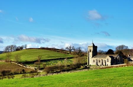 Quaint English rural stone church in Crosthwaite, Cumbria, England, set amongst rolling green hills. Stock Photo
