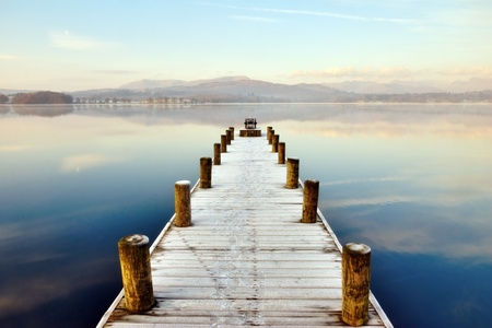 cumbria: Jetty At Windermere, English Lake District, Cumbria, England, extending out in to a peaceful lake with distant hills.