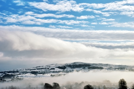 sub zero: Winter cloud and mist over low lying farmalnd blanketed in snow with blue sky above. Stock Photo