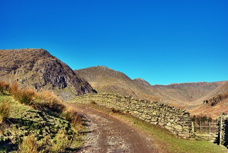 Deserted gravel farm track alongside an old stone wall leading to rolling mountains in Kentmere, English Lake District photo