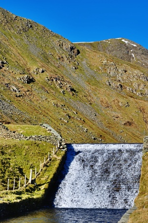 regulate: Water flowing over a sluice and spillway to regulate the rate of flow in Kentmere, English Lake District Stock Photo