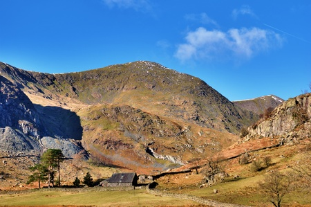 sloping: Picturesque farm buildings below sloping green foothills in Kentmere, English Lake District
