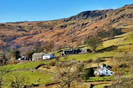 english countryside: Picturesque farm buildings on sloping green foothills in Kentmere, English Lake District Stock Photo