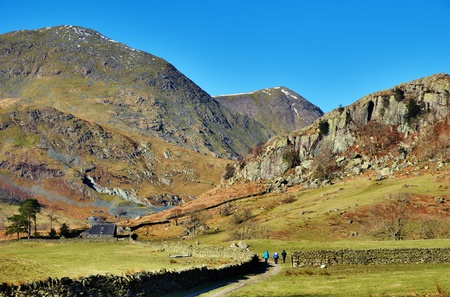 valley below: Hikers walking through a green valley past an old agriculrural barn below mountain peaks in Kentmere, English Lake District