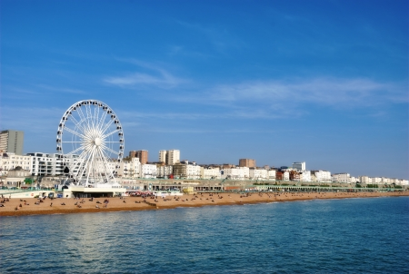 Panoramic view along Brighton Beachfront with the promenade and Ferris Wheel backed by highrise buildings