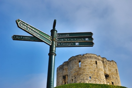 loopholes: A signpost and Cliffords Tower against blue sky showing the quatrefoil design of the keep and the distinctive shape of the loopholes for firing at the enemy