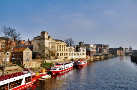 ouse: Colourful passenger ferries moored on the bank of the River Ouse in York waiting to take tourists on a sightseeing cruise Stock Photo