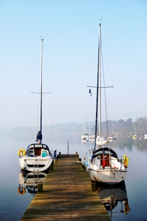 moorings: Two small pleasure yachts moored alongside a rustic wooden jetty with mist hanging over the water in Windermere, English Lake District
