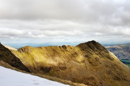 valley below: Sharp edged ridge leading to a peak with a view toward the valley below