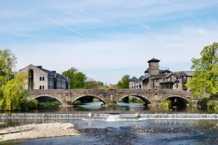 The medieval arched structure of Stramongate bridge and weir at Kendall on the river Kent with historical stone buildings on the riverbanks Stock Photo