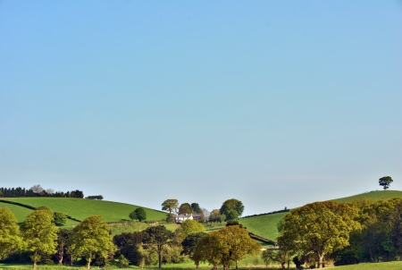 Rolling English hills and lush farmland with a small farmhouse nestled between the folds of the hills looking down onto a treed valley photo