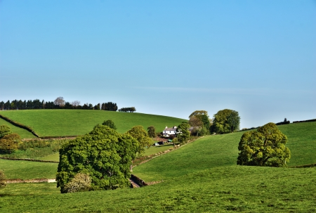 Remote whitewashed farmhouse in the gently rolling hills of the lush green English countryside photo