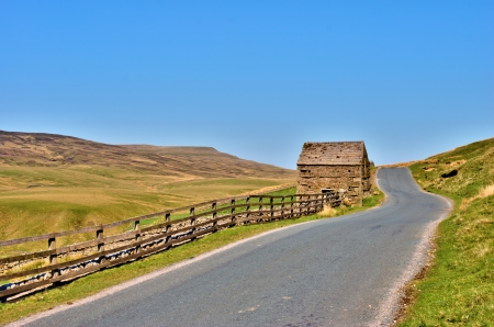 Deserted country road with a rustic wooden fence and an old stone barn alongside it leading though fields up over a gentle hill photo