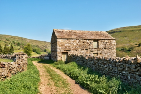 Farm track leading past an old barn and dry stone wall in the Yorkshire Dales, England photo