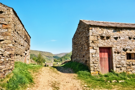 Yorkshire Dales: Deserted farm track leading between two stone barns towards the rolling hills of the Yorkshire Dales