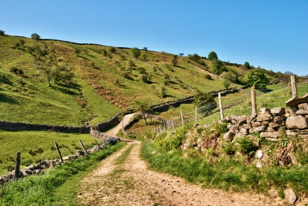 Deserted winding gravel farm track meandering up over a gentle hill in the Yorkshire Dales national park photo