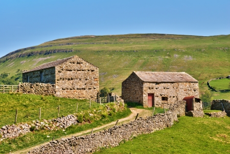 Picturesque old stone barns on a farm in the rolling hills of the Yorkshire Dales, England photo