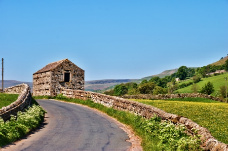 drystone: Curving deserted picturesque English country road bounded by dry-stone walls with a quaint old stone barn in Swaledale, Yorkshire Dales Stock Photo