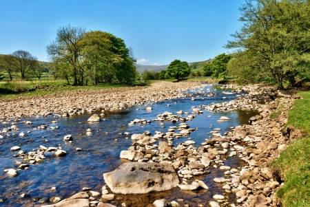 unspoilt: Low angle view of the clean frsh water of the River Swale flowing through the lush English countryside of the Yorkshire Dales