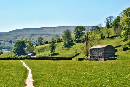 Yorkshire Dales: Remote farm track leading through green fields past an old agricultural barn in Swaledale, Yorkshire Dales Stock Photo