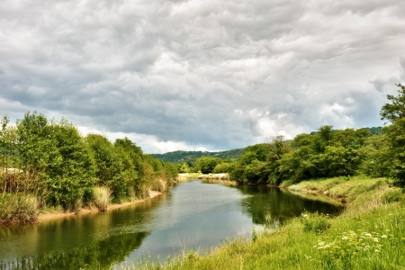 Calm waters of the River Leven flowing through lush countryside under a cloudy sky, Haverthwaite, Cumbria , England Stock Photo