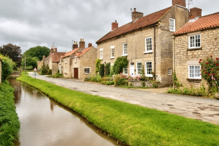 A row of picturesque cottages and stream in the touristic Yorkshire village of Hovingham, Northern England Stock Photo