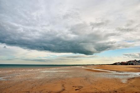 The sandy beach and shore at Bridlington, England under a cloudy sky Stock Photo - 14839477