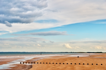 A couple walking on a deserted sandy beach in the English seaside resort of Bridlington  Stock Photo - 14839479