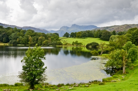 langdale pikes: Loughrigg Tarn and the Langdale Pikes in the English Lake District under a stormy sky