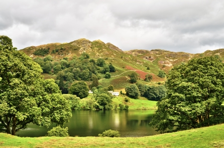 Loughrigg tarn, English Lake District, Cumbria, England, a natural lake nestling in the mountains in a hollow cirque formed by ancient glaciers Stock Photo - 15845329